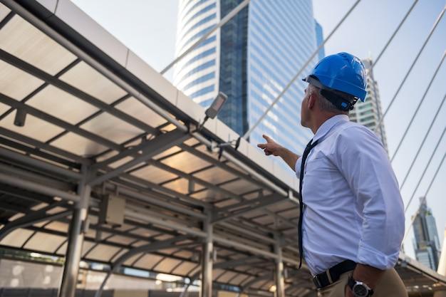 Il vecchio consulente di ingegneria americano con i capelli grigi e il casco puntano il dito verso la costruzione del cantiere nella città moderna.
