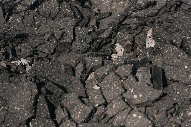 Il vecchio danno incrinato dello scrapheap della strada asfaltata sulla terra da riciclare. accetta per ridurre il riutilizzo e ricicli. primo piano di vecchio asfalto incrinato fuoco selezionato. trama di sfondo grigio