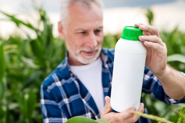 Il vecchio in un campo si guarda una bottiglia tra le mani. mockup di bottiglia di fertilizzante