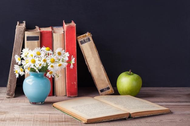 Il vecchio libro d'annata aperto si trova su una tavola rustica di legno. paese ancora vita.