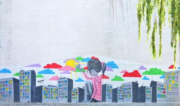 Il vecchio muro, dipinto a colori con disegni di graffiti e colori spray. immagine di una bambina che disegna molti grattacieli con un pennello con vernici