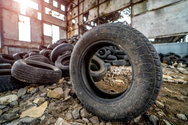 Il vecchio pneumatico sporco è a terra in piedi accanto agli altri pneumatici usati nella pianta danneggiata.