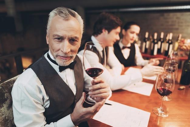 Il vecchio sommelier esperto sta tenendo il bicchiere di vino rosso.