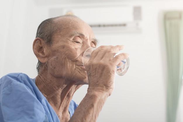 Il vecchio tiene e beve un bicchiere d'acqua