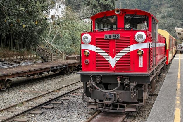 Il vecchio treno rosso in alishan line ritorna alla stazione ferroviaria di chiyi in una giornata nebbiosa.