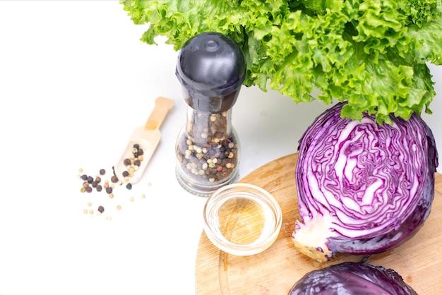 Il vegetarianismo. ingredienti per un'insalata leggera. cavolo, lattuga, piselli e olio d'oliva porpora su una tavola bianca.