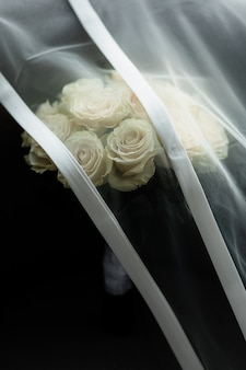 Il velo da sposa copre il bouquet di rose nuziali