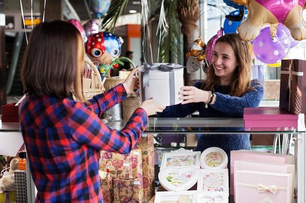 Il venditore del regalo della donna sta dando la scatola