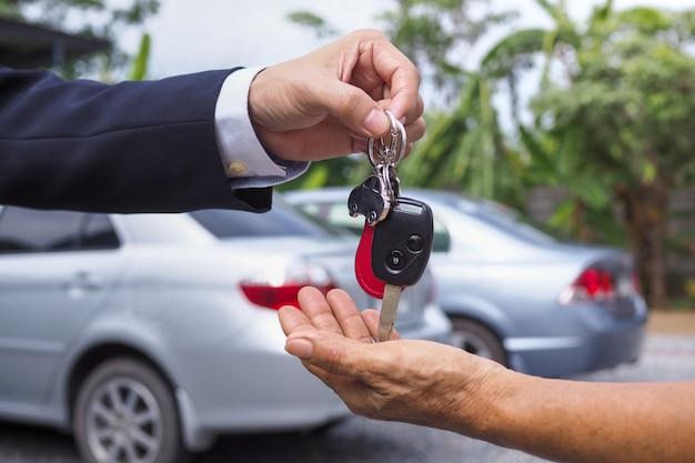 Il venditore di auto ha inviato le chiavi al nuovo proprietario dell'auto. comprare e vendere il concetto di noleggio