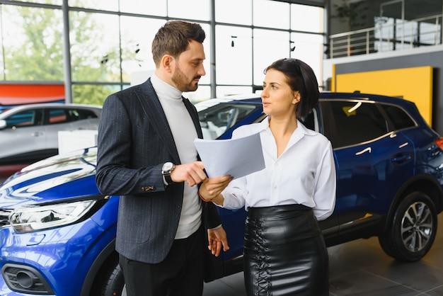 Il venditore e l'acquirente nel salone dell'auto
