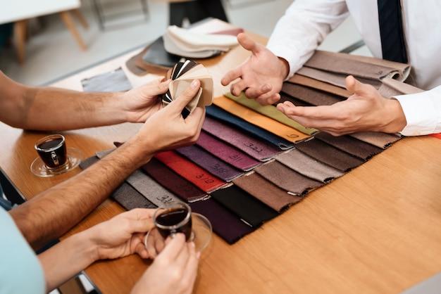 Il venditore mostra campioni di materiali per mobili.