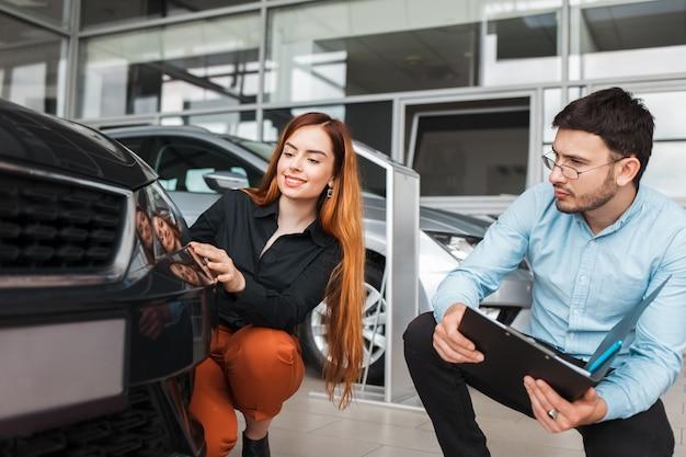 Il venditore mostra l'auto a un giovane cliente