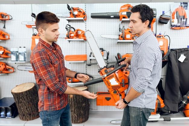 Il venditore nel negozio mostra ai clienti una motosega.