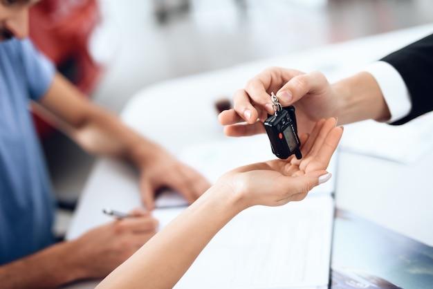 Il venditore nello showroom di auto consegna le chiavi dell'auto all'acquirente.