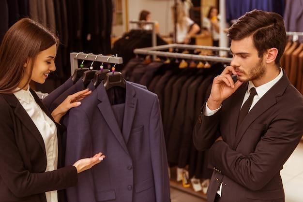 Il venditore ragazza aiuta un uomo a scegliere un abito.