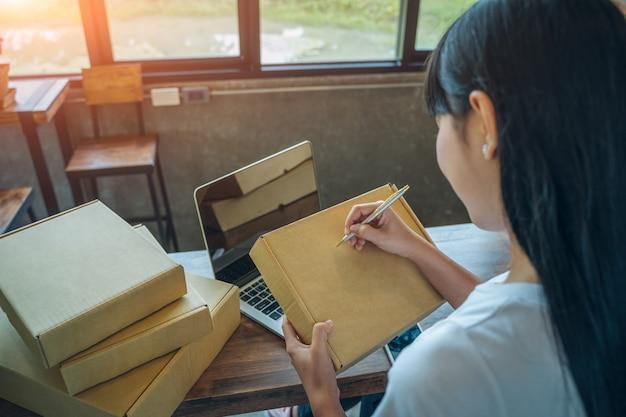 Il venditore sta preparando prodotti da consegnare ai propri clienti, vendite online o e-commerce. visione del concetto di corsi su internet con un'interfaccia tecnologica - concetto di vendita