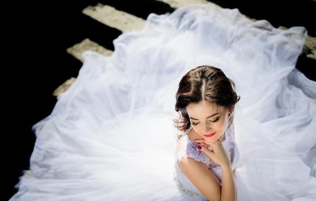 Il vento soffia il vestito della sposa mentre lei sta sulle orme rovinate