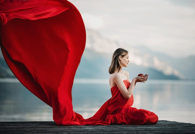 Il vento soffia il vestito rosso di una donna incinta che si siede con la mela sul ponte sul lago