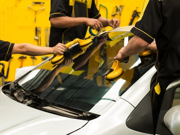 Il vetraio sta riparando il parabrezza dell'auto