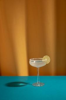 Il vetro del cocktail della margarita guarnisce con calce sulla tavola blu contro la tenda gialla
