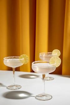 Il vetro del cocktail della margarita guarnisce con calce sulla tavola contro la tenda gialla