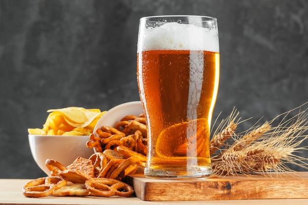 Il vetro di birra con bretzel e gli spuntini secchi delle salsiccie si chiudono su