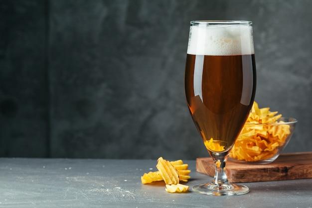 Il vetro di birra scura con la ciotola di spuntini della birra si chiude su