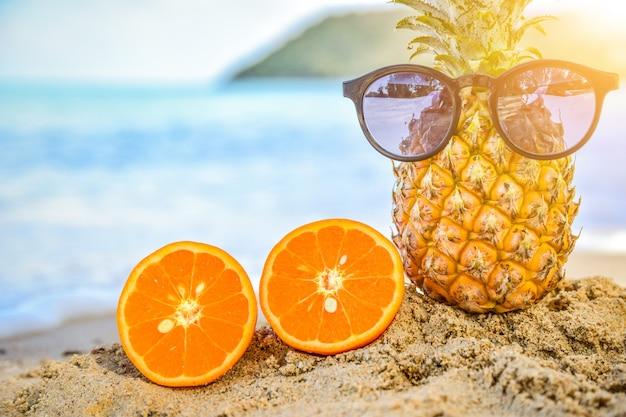 Il vetro di sun è su ananas al fondo di vista del mare della spiaggia, concetto di vacanza estiva