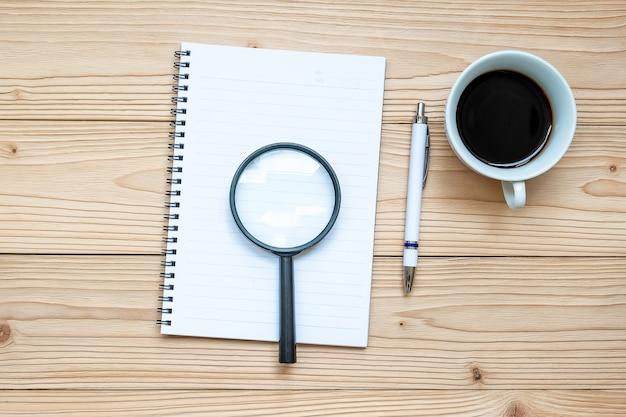 Il vetro ingrandice, taccuino, penna e caffè nero su fondo di legno