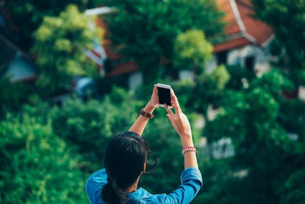 Il viaggiatore asiatico della donna nella vista usata della parte posteriore legge lo smart phone