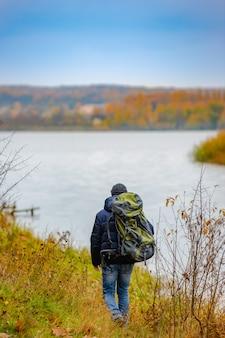Il viaggiatore con uno zaino passa lungo la collina vicino al fiume in autunno