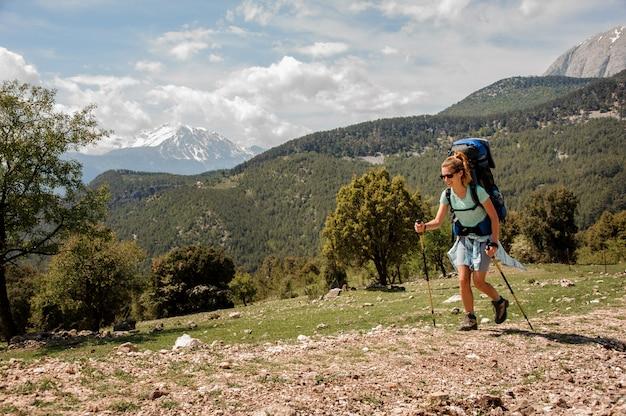 Il viaggiatore con zaino e sacco a pelo femminile viaggia giù per la strada in collina