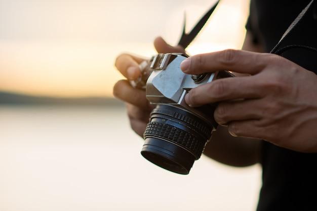 Il viaggiatore con zaino e sacco a pelo si rilassa sulla montagna con la macchina fotografica e il tramonto