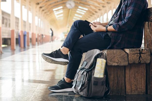 Il viaggiatore del giovane che si siede con l'utilizzo del telefono cellulare sceglie dove viaggiare e borsa aspettando il treno alla stazione ferroviaria. imballatore alla stazione ferroviaria e cercando sul telefono cellulare il piano di viaggio.