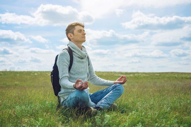 Il viaggiatore dell'uomo con lo zaino si siede sul prato con erba verde sotto cielo blu con le nuvole nella posizione di lotus