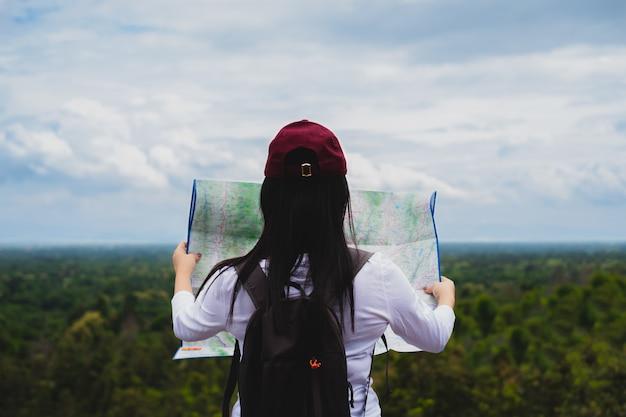 Il viaggiatore della giovane donna con lo zaino che sta la tenuta e guarda la mappa sul campeggio della montagna di viaggio