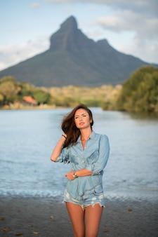 Il viaggiatore della giovane donna sta sulla spiaggia contro la montagna e gode della bellezza del paesaggio del mare. la giovane donna ama la vita selvaggia, i viaggi, la libertà.