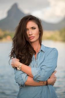Il viaggiatore della ragazza sta sulla spiaggia contro la montagna e gode della bellezza del paesaggio del mare. la ragazza ama la vita selvaggia, i viaggi, la libertà.
