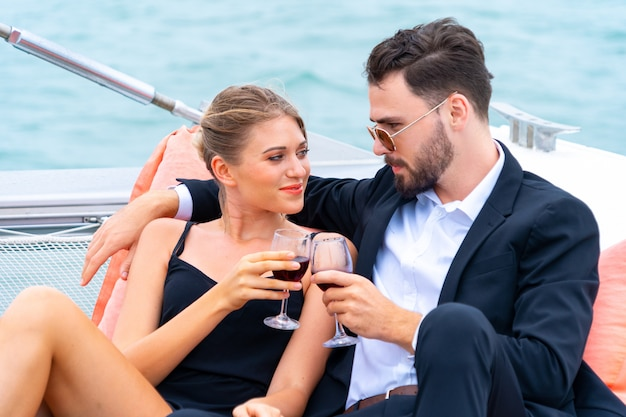 Il viaggiatore di lusso rilassante delle coppie in vestito e suite piacevoli si siede sul sacchetto del fagiolo e beve un bicchiere di vino in parte dell'yacht di crociera.