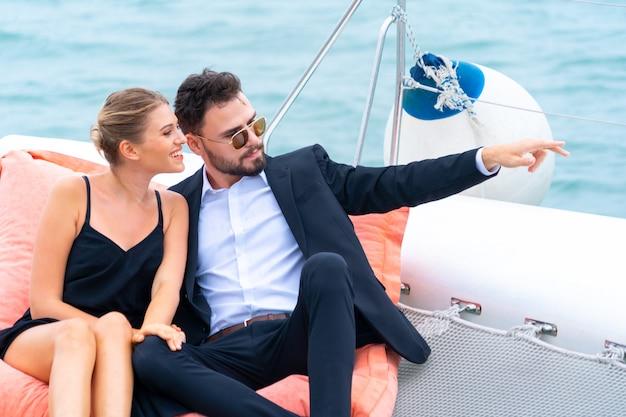 Il viaggiatore di rilassamento di lusso delle coppie in vestito e suite piacevoli si siede sul sacchetto di fagiolo nella parte dell'yacht di crociera con fondo del mare e del cielo bianco. viaggi d'affari di concetto.