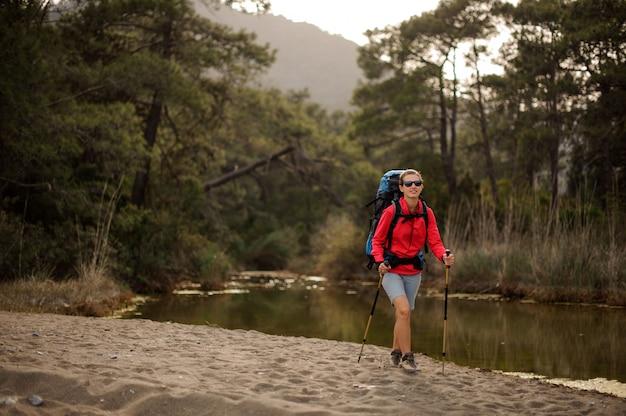 Il viaggiatore femminile cammina dalla riva del fiume della foresta