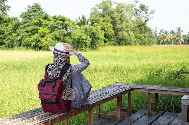 Il viaggiatore femminile musulmano gode della vista del cottage bello del campo naturale