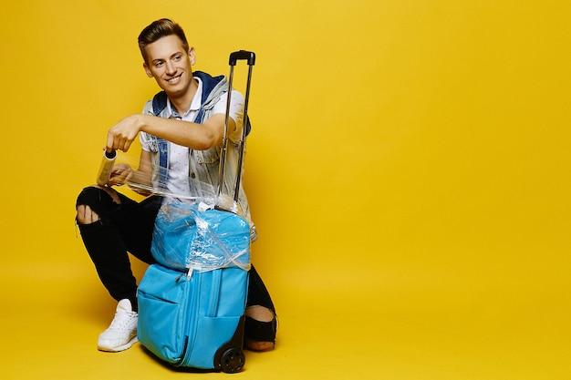 Il viaggiatore maschio con una valigia lo sta preparando per consegnarlo nel bagaglio al check-in in aeroporto