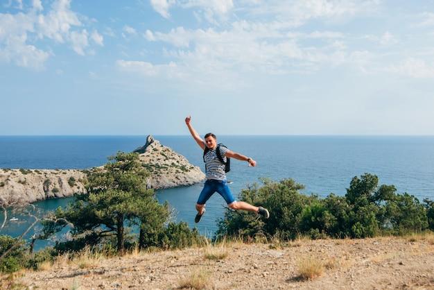 Il viaggiatore maschio salta allegramente e felicemente nella natura