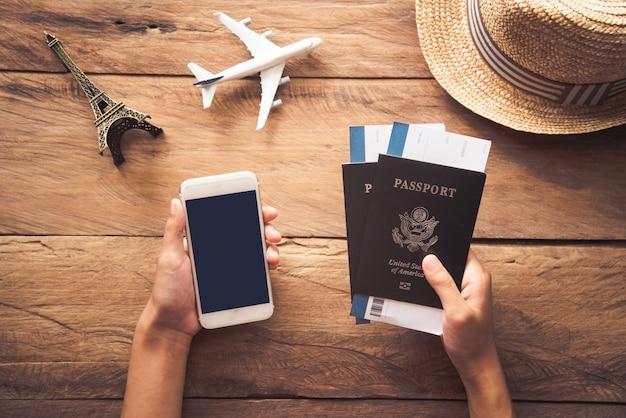 Il viaggiatore tiene passaporto e smart phone. insieme al viaggio