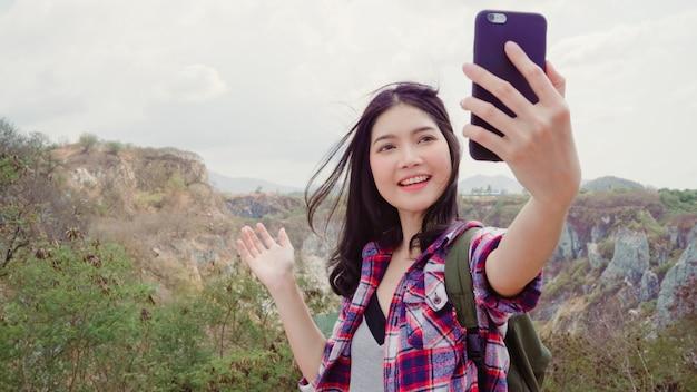 Il video asiatico del vlog della donna di viaggiatore con zaino e sacco a pelo di blogger sopra la montagna, giovane femmina felice facendo uso del telefono cellulare fa il video del vlog gode delle feste sull'escursione dell'avventura.