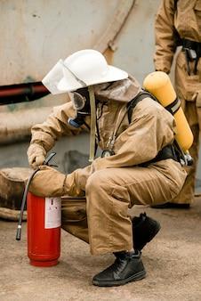 Il vigile del fuoco controlla la sua attrezzatura e l'estintore durante l'allenamento