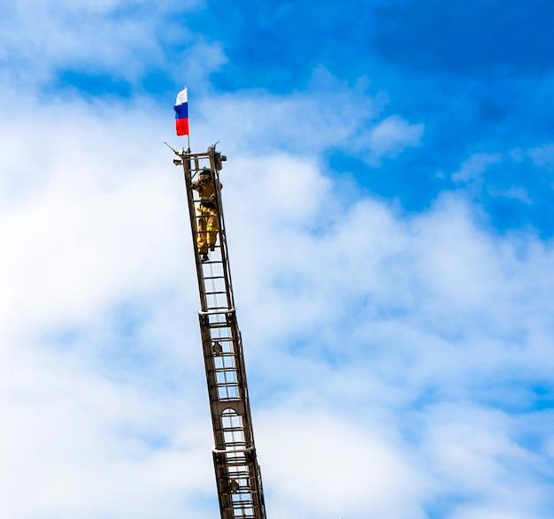 Il vigile del fuoco su una lunga scala antincendio contro il cielo blu alza la bandiera