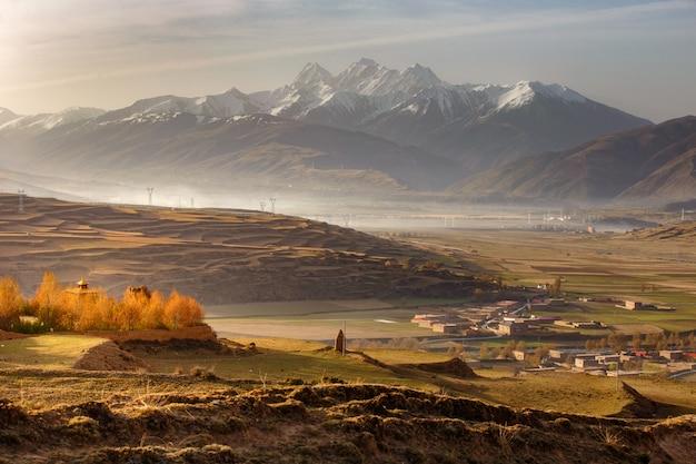 Il villaggio inclose la montagna un punto di riferimento famoso in ganzi, sichuan, cina.