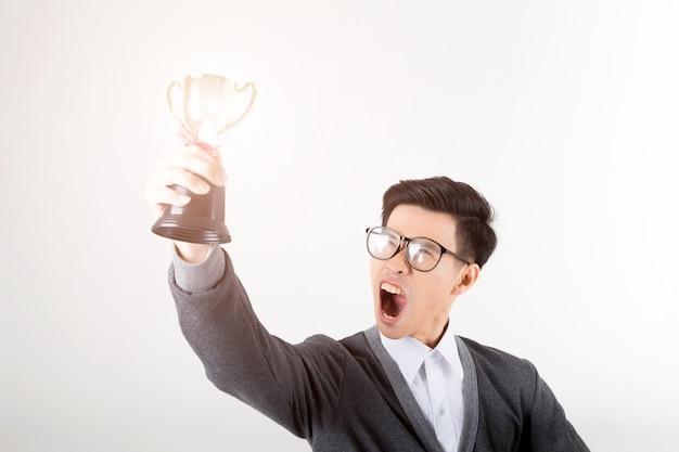 Il vincitore che tiene il trofeo d'oro. studio sparato su priorità bassa bianca.